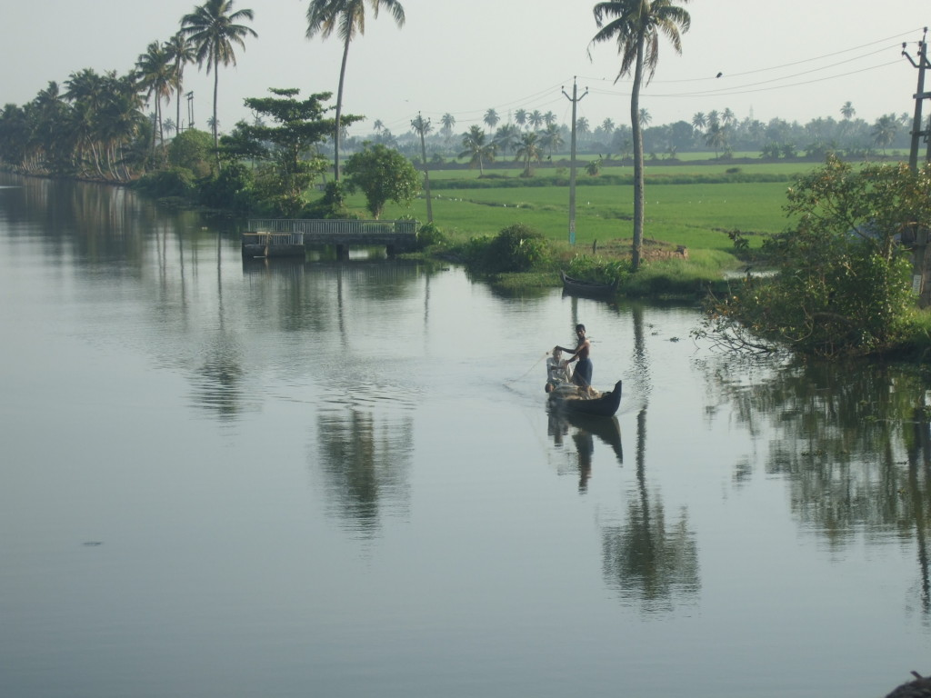 A lone fishing boat parts the still waters near Lake Vembanad in early morning.