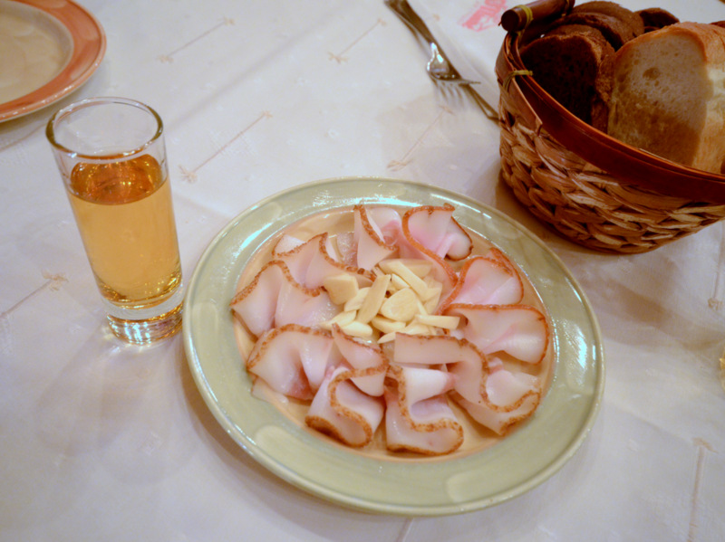A plate of salo - pork fat served with slivers of fresh garlic and a shot of flavored vodka on the side.
