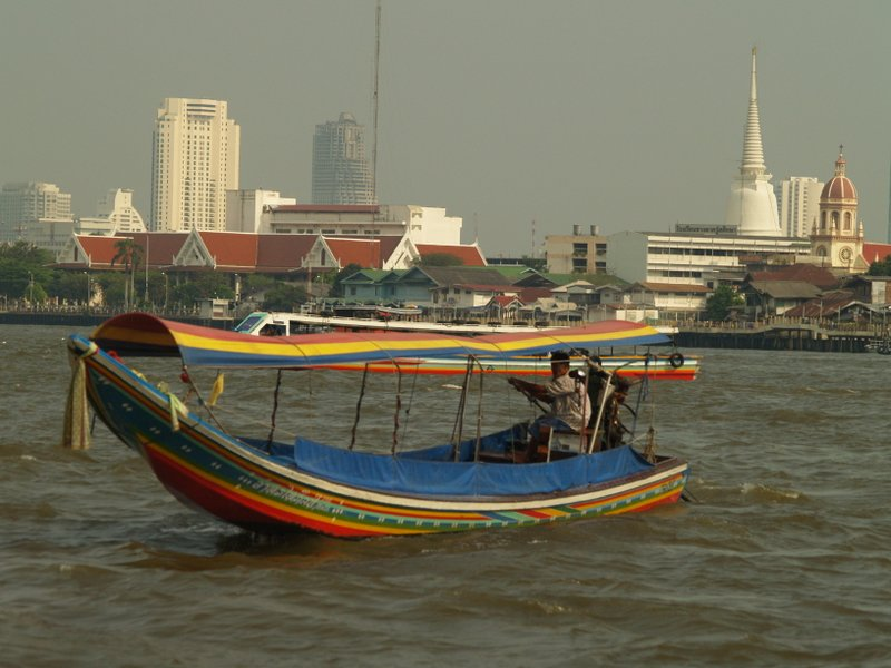 A longtail boat works the Chao Phraya River.